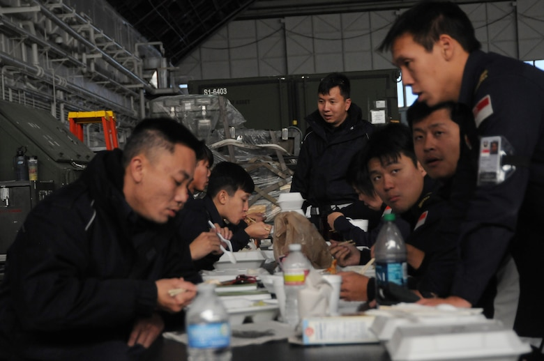 "Ground crew personnel from the 428th Fighter Squadron from Mountain Home Air Force Base, Idaho, eat lunch after spending the morning preparing aircraft for launch Oct. 12, 2012, at Eielson Air Force Base, Alaska. Lunchtime between ""sorties"" is greatly appreciated as it gives them an opportunity to warm up and unwind from their hectic work environment on the flight line. (U.S. Air Force photo/Senior Airman Benjamin Sutton/Released)"