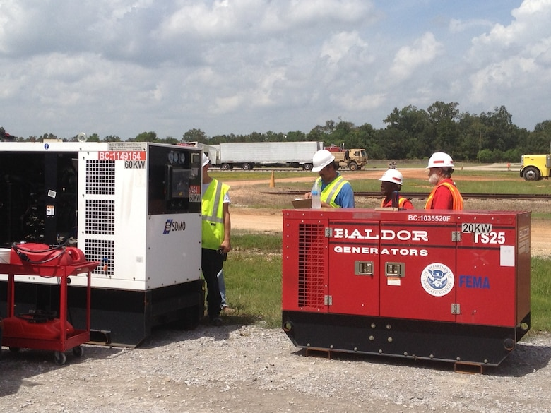 Left to right, a power contractor representative, Arthur Miller and Jack Wilkerson prepare 20 and 60 kilowatt emergency generators for return to storage as the emergency power mission ramps down.