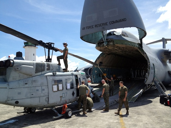 "U.S. Marines with Detachment Martillo load a UH-1N ""Huey"" helicopter on an Air Force C-5 ""Galaxy"" at La Aurora International Airport in Guatemala City Oct. 12, en route back to the United States.  The task-organized detachment partnered with Guatemala authorities to disrupt illicit trafficking in the country's coastal waters. With four Huey's, Detachment Martillo flew over 250 detection and monitoring missions in support of Guatemalan law enforcement agencies and naval forces during the roughly two-month deployment.  ""We saw an immediate impact in trafficking patterns along established routes after we started flying our helos,"" said Col. Rob Rauenhorst, the Detachment Martillo officer-in-charge.  (U.S. Marine Corps Photo by Capt. Greg Wolf)"