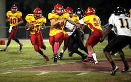 Lejeune High School's running back Jamaz Richardson runs the ball to the outside as fullback Stephen Dicenso looks for a defensive player to block against the Pamlico County High School Hurricanes during Lejeune High's homecoming game aboard Marine Corps Base Camp Lejeune Friday. Lejeune High School was able to effectively run the ball throughout the game, as Richardson rushed for 260 yards and three touchdowns. (Official Marine Corps photo by Lance Cpl. Scott W. Whiting)