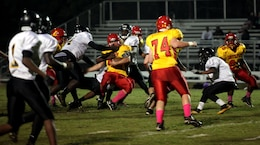 Stephen DiCenso, fullback for the Lejeune High School Devil Pups, gets tackled by three Pamlico County High School defenders after running the ball during the Devil Pups homecoming game Friday. The Devil Pups, as a team, rushed for 370 yards during the game, and DiCenso scored a touchdown along with 53 yards on the ground. (Official Marine Corps photo by Lance Cpl. Scott W. Whiting
