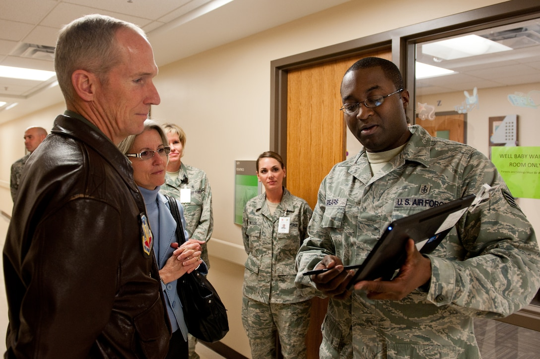 Air Force Staff Sgt. Kevin Spears, 28th Medical Operations Squadron information systems NCO in charge, explains how the 28th Medical Group and providers use a tablet to document a patient's care during an exam to Gen. Mike Hostage, commander of Air Combat Command, and his wife, Kathy, in the clinic at Ellsworth Air Force Base, S.D., Oct. 10, 2012. Hostage and his wife toured the facility and viewed some of its modern additions including a mobile storage device for the supply room that saves more than 30 percent in the amount of space used. (U.S. Air Force photo by Airmen 1st Class Kate Thornton-Maurer/ Released)