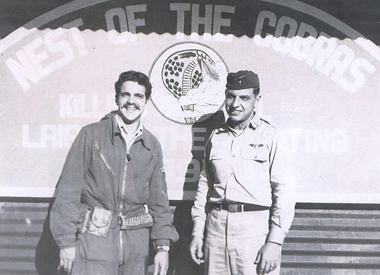 John Taylor (left) and Ernest Wakehouse stand in front of the 39FIS operations shack at an airfield in the Republic of Korea, 1951.