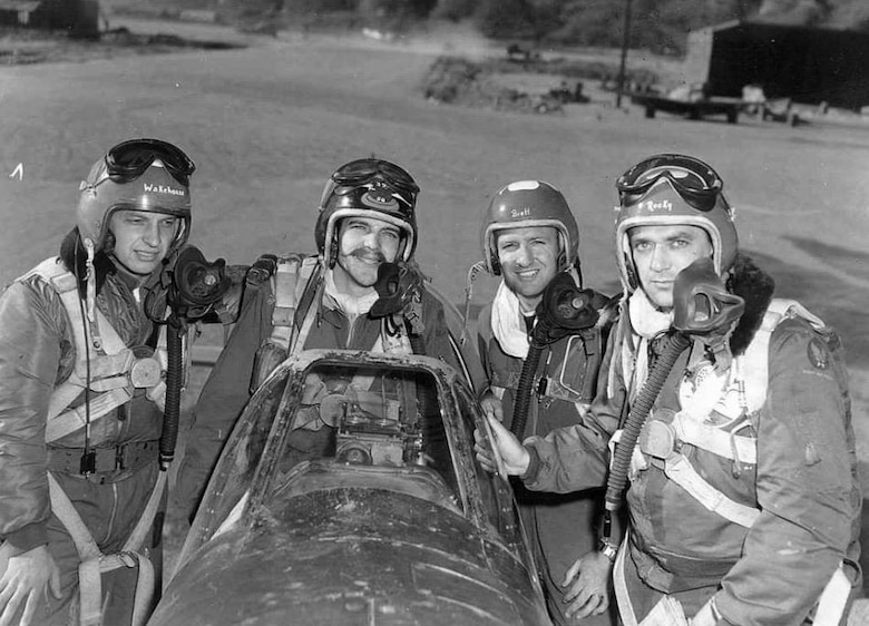 "From left to right, Ernie Wakehouse, John ""JET"" Taylor, Devol ""Rock"" Brett, and Fred Rockmaker of the 39th Fighter Interceptor Squadron pose for the camera on an F-51 Mustang at an airfield in the Republic of Korea, possibly K-46, Hoengsong, 1951."