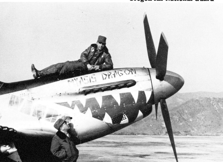 "Ore ANG pilot Ernest Wakehouse strikes a leisurely pose atop the nose of a Mustang in Korea during a break in operations.  But combat flying wasn't  leisurely at all and the name on the plane, ""Myasis Dragon,"" described how he felt at times during his combat tour.  Another F-51 pilot, possibly Wallace Parks, looks on."