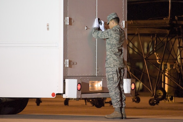 Senior Airman Joshua Fernandez closes the door of the transfer vehicle during a dignified transfer Nov. 13, 2011, at Dover Air Force Base, Del. Fernandez has served in a variety of positions inside the Charles C. Carson Center for Mortuary Affairs during his deployments in support of the sacred mission. Fernandez is assigned to the 512th Memorial Affairs Squadron at Dover AFB. (U.S. Air Force Photo/Adrian Rowan)