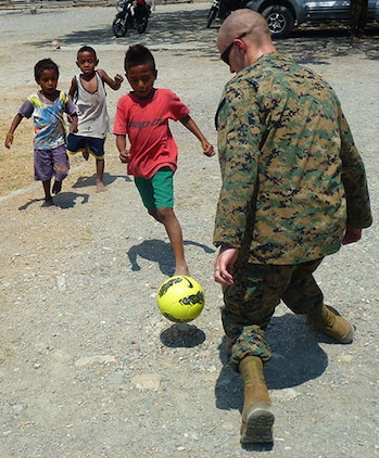 Sgt. Nicholas O. Troyer, data chief, Battalion Landing Team 3/5, 15th Marine Expeditionary Unit, plays soccer with Timorese children after fellow Marines and sailors presented books, school supplies and sporting goods to their elementary school in Manatuto, Timor-Leste, Oct. 14. The donations were part of a community relations program supporting Exercise Crocodilo 2012, a U.S./Timor-Leste event promoting interoperability and regional stability.