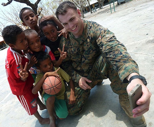 Staff Sgt. Harry G. Prassenos, operations chief, Military Information Support Operations Detachment, 15th Marine Expeditionary Unit, takes a picture with Timorese children after fellow Marines and sailors presented books, school supplies and sporting goods to their elementary school in Manatuto, Timor-Leste, Oct. 14. The donations were part of a community relations program supporting Exercise Crocodilo 2012, a U.S./Timor-Leste event promoting interoperability and regional stability.