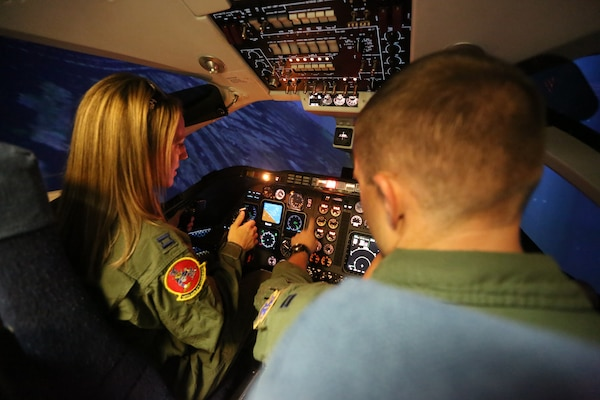 Capt. Cory Henwood, 99th Flying Training Squadron T-1A Jayhawk instructor training pilot, demonstrates to his wife, Rebekah Henwood, what it is like to fly in a simulator, during the 99th FTS Annual Spouse Appreciation day Oct 5. at Joint Base San Antonio-Randolph. Spouses who attended learned about their partner's and other squadron members roles in the Air Force mission. (U.S. Air Force photo by Josh Rodriguez)