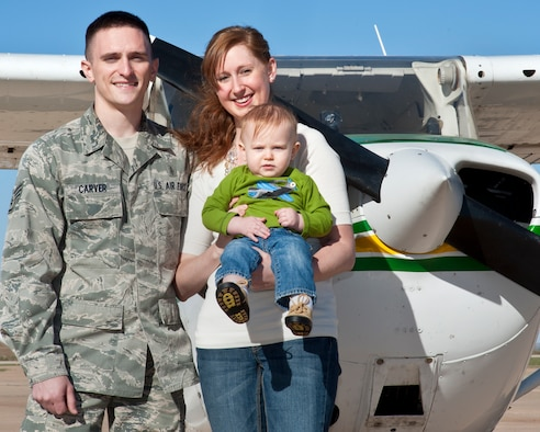ALTUS, Okla. -- Staff Sgt. Nicholas Carver, 97th Medical Support Squadron NCO in charge of central appointments and patient travel, his wife Sarah and son, Skylar, pose for a photo in front of a Cessna 172 Skyhawk aircraft at the Altus/Quartz Mountain Regional Airport Oct. 18, 2012. Carver was recently selected to attend Officer Training School and is scheduled to attend Undergraduate Pilot Training afterwards. (U.S. Air Force photo by Senior Airman Kenneth W. Norman / Released)