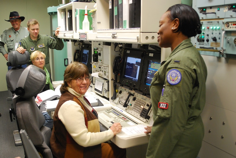 "1st Lt. Arielle Wallace, 341st Operations Support Squadron instructor deputy combat crew commander, far right, and Capt. Nicholas Edwards, 341st OSS instructor combat crew commander, explain the next step of a ""key turn"" to two members who toured the Missile Procedures Trainer on Oct. 11 during the 50th Anniversary celebration.  Both women operating the MPT are spouses to retired Air Force members who once operated the same systems; on the left consol is Kay Williams, wife to retired Col. Ronald Williams, and on the right consol is Mickey Livingston, wife to retired Col. Doug Livingston (pictured in background).  (U.S. Air Force photo/Airman 1st Class Cortney Paxton)"