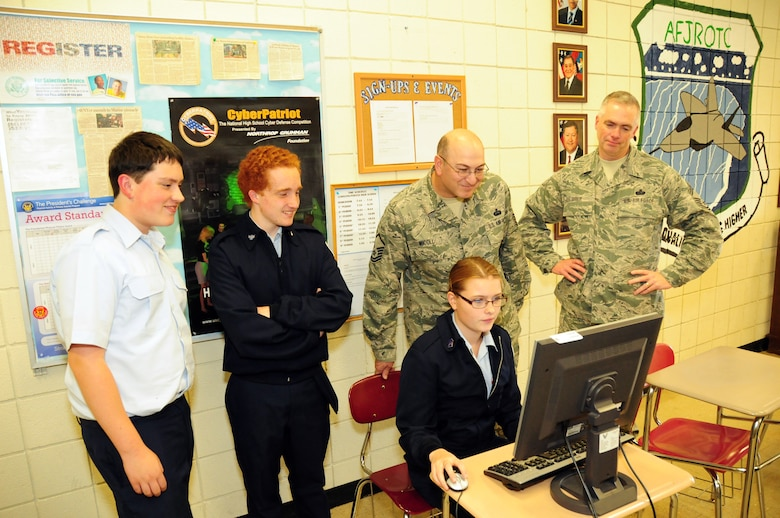 Once again the 107th Airlift Wing steps up. This time it's to mentor our young Junior Reserve Officer Training Corps (JROTC) at the Lewiston-Porter High School. The mission is called CyberPatriot. Brian Boyd, Matt O'Conner, Master Sgt. Joel Micoli and Chief Master Sgt. Mark Grier observed Ashlee Roell performing her cybersecuirty task on Oct, 16, 2012. (U.S. Air Force Photo/Senior Master Sgt. Ray Lloyd)