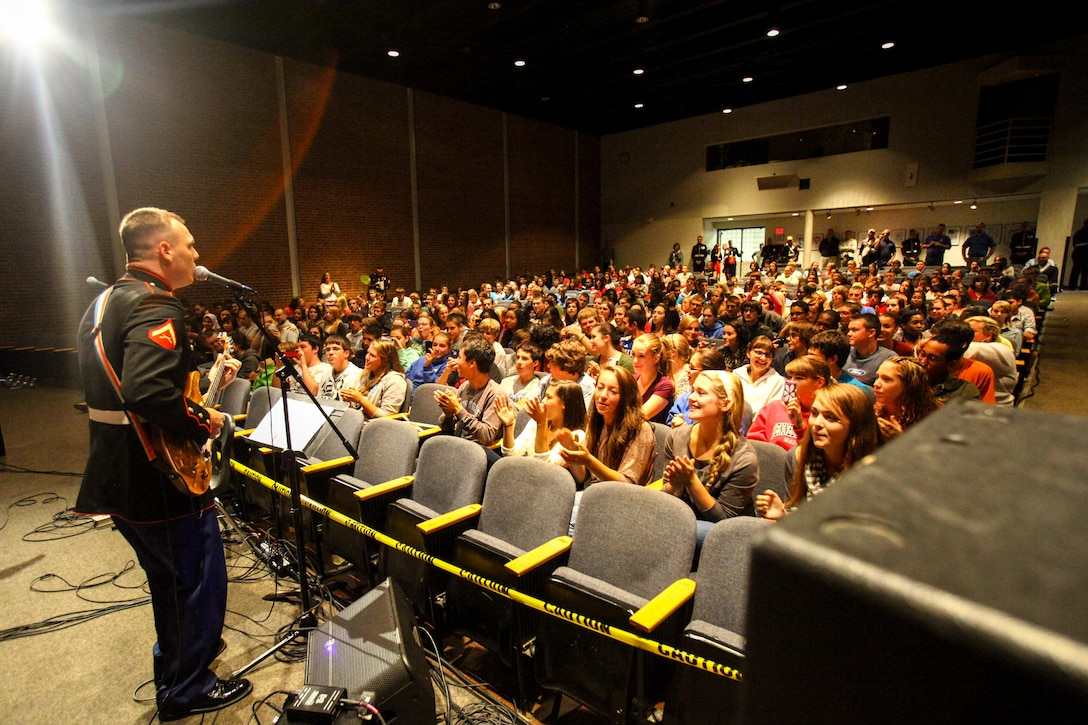 Lance Cpl. David Corderman of Richmond, Va., sings in front of hundreds of high school students.  He and two other Marines within the band took the initiative to come together and form the 2nd Marine Division rock band.
