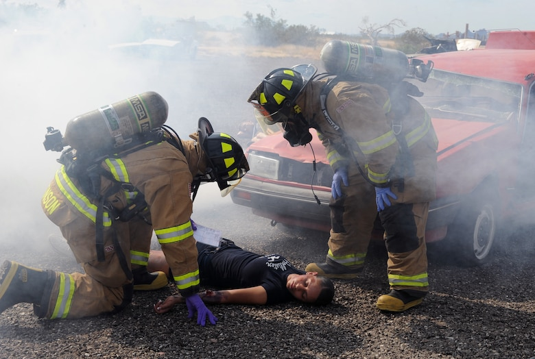 Members of the 355th Civil Engineer Squadron read a card with symptoms of a simulated victim of an explosion during the Response Training and Assessment Program exercise on Davis-Monthan Air Force Base, Oct. 17, 2012. Davis-Monthan is one of three instillations needed to validate the RTAP training and exercise program to meet the requirements for Headquarters Air Force. (U.S. Air Force photo by Senior Airman Brittany Dowdle/release)
