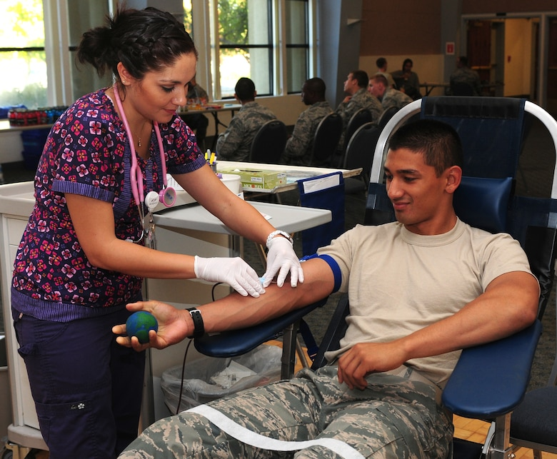 Valorie Guerra, Blood Source phlebotomist, takes a blood donation from Airman Basic Raymond Rubio, 372th Training Squadron crew chief student, at the Beale Air Force Base, Calif. community activity center Oct. 19, 2012. Blood donations provide life-saving treatments to accident victims, surgery patients, cancer patients and many others in need of a transfusion. (U.S. Air Force photo by Senior Airman Allen Pollard)