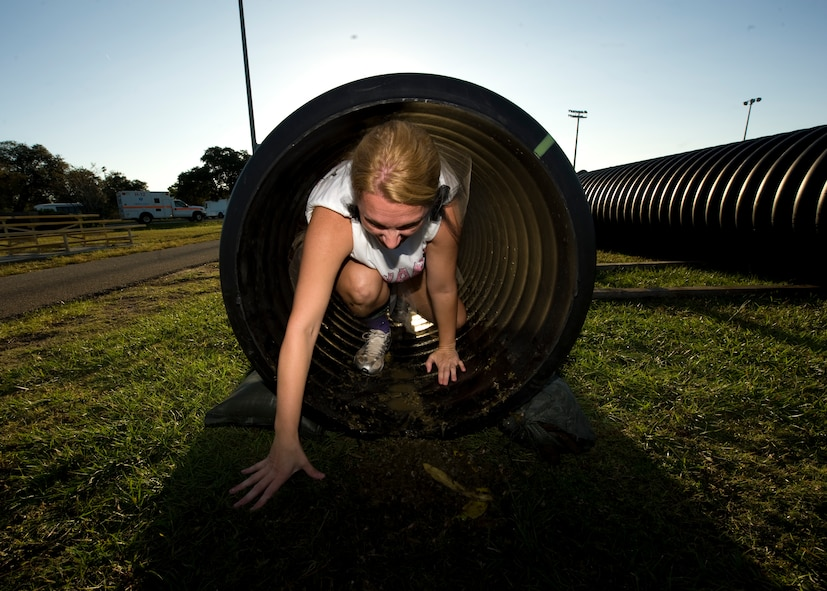 U.S. Air Force Master Sergeant Sonia Poulin, first sergeant of  1st Special Operations Comptroller Squadron, crawls through a tube filled with rotten food during the Carnivore Confidence Course at Hurlburt Field, Fla., Oct. 19, 2012. MSgt. Poulin is in one of many teams participating in the morale building exercise. (U.S. Air Force Photo/ Airman 1st Class Nigel Sandridge)