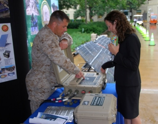 Major Jesse Hardin, Marine Corps Systems Command's (MCSC) Energy Systems Branch Head, talks with a visitor at MCSC's Marine Corps Expeditionary Energy display in the Pentagon Courtyard during the Pentagon Energy Security Event in early October.