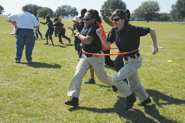 Tonette Gezzi and Angela Dunwoodie, members of the Civilian Police Working Dogs Section, race to the finish line during a hula hoop relay at Marine Corps Logistics Base Albany's Employee Recognition Day, Oct. 11.