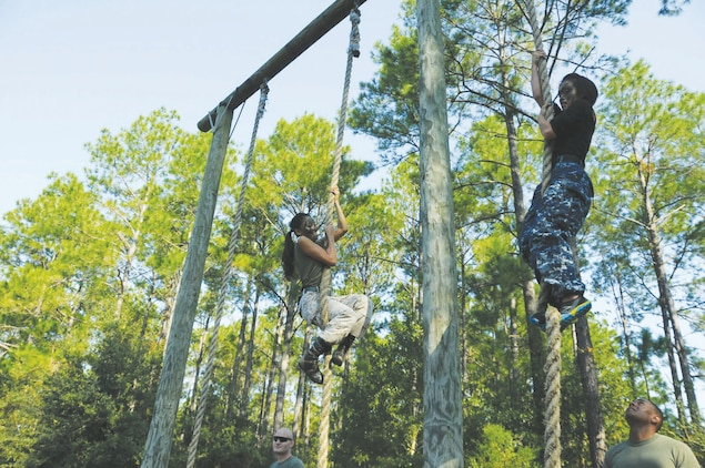 Spouses of Marines and Sailors test their skills in a rope climb during Jane Wayne Day, Oct. 12, at Marine Corps Logistics Base Albany. Jane Wayne Day is designed for spouses and guests of service members to gain a better appreciation for, and understand, military training events and activities. Spouses and guests are afforded an opportunity to be pushed and trained by subject matter experts in different events.