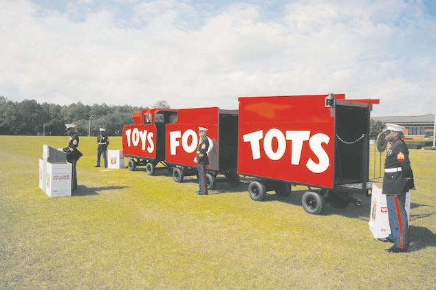 Marines with Detachment 2, Supply Company, 4th Supply Battalion, 4th Marine Logistics Group, stand next to the newly-refurbished Toys for Tots train during their annual Tots for Tots kickoff in front of Building 3500, Monday. They will showcase it at distribution sites and fundraisers throughout the campaign.