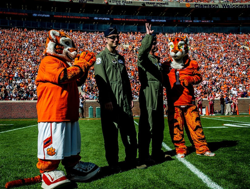 Capt. Justin Kulish (left) and Capt. Michael Polidor (right), B-2 Bomber pilots from Whiteman Air Force Base, Mo., stand with mascots from the Clemson Tigers during a ceremony Oct. 20, 2012, at Memorial Stadium, Clemson S.C. The two pilots were recognized for their efforts providing close-air support during an insurgent ambush of Command Outpost Keating in October 2009. (U.S. Air Force photo/Senior Airman Dennis Sloan)