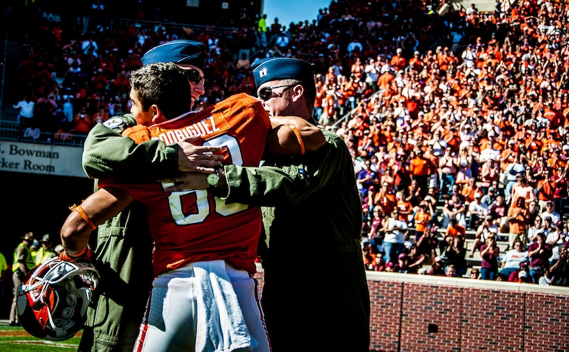 Former Army Sgt. Daniel Rodriguez, now a wide receiver for the Clemson tigers, hugs Air Force Capt. Justin Kulish (left) and Air Force Capt. Michael Polidor (right), both B-2 Bomber pilots from Whiteman Air Force Base, Mo., during a ceremony Oct. 20, 2012, at Memorial Stadium, Clemson S.C. The two pilots were recognized for their efforts providing close-air support during an insurgent ambush of Command Outpost Keating in October 2009. Rodriguez was deployed to the outpost during the attack. (U.S. Air Force photo/Senior Airman William O'Brien)