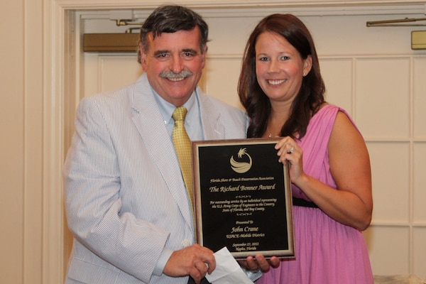 John Crane, a Mobile District project manager, holds the Richard E. Bonner Award with Lisa Armbruster, beach management consultant and government affairs liaison for the Florida Shore & Beach Preservation Association. Photo courtesy of FSBPA.