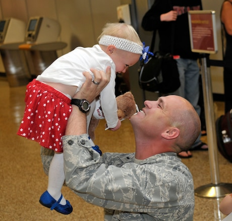 1st Lt. Brian Herrscher, 130th Engineering Installation Squadron, greets his daughter at the Salt Lake City International Airport after returning from a six-month deployment to the Middle East on Sunday Oct. 21, 2012. Herrscher, along with 13 others from the 130th EIS were deployed to the Middle East in support of Operation Enduring Freedom. (U.S. Air Force Photo by Tech. Sgt. Jeremy Giacoletto-Stegall/Released)