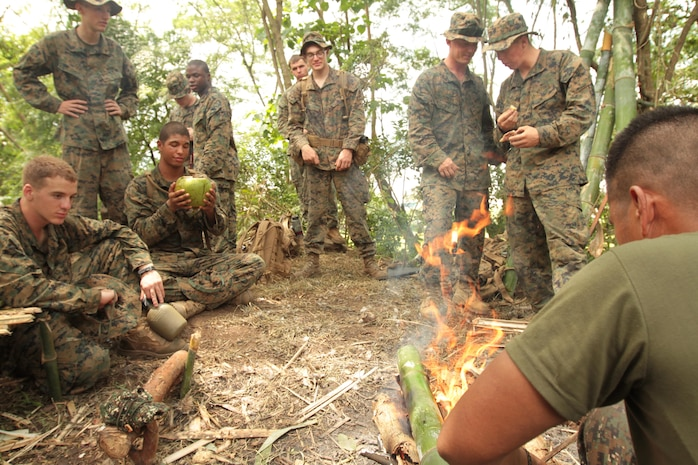 CROW VALLEY, Republic of the Philippines - Marines and Sailors with Company G., Battalion Landing Team 2nd Battalion, 1st Marine Regiment, 31st Marine Expeditionary Unit, consolidate around a fire, learning how to cook rice inside a bamboo trunk during a jungle survival class instructed by Philippine Marines here, Oct. 12. The event is part of the 29th iteration of the Amphibious Landing Exercise, designed to increase the interoperability of the forces and strengthen their long standing bond. The 31st MEU is the only continuously forward-deployed MEU and is the Marine Corps' force in readiness in the Asia-Pacific region.
