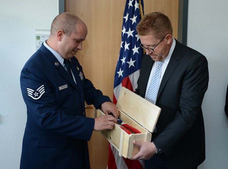 SPANGDAHLEM AIR BASE, Germany – Marco Haas presents a bayonet to U.S. Air Force Staff Sgt. Scott Martin, 606th Air Control Squadron radio frequencies transmissions systems operator from Chico, Calif., during a ceremony at the 606th ACS Oct. 4, 2012. The bayonet belonged to U.S. Army Pfc. Clyde Sparks, the grandfather of Martin's wife, Jessica, who fought in Luxembourg during World War II. Martin accepted the bayonet on behalf of his wife's family, who were unable to attend the ceremony. (U.S. Air Force photo by Staff Sgt. Nathanael Callon/Released)