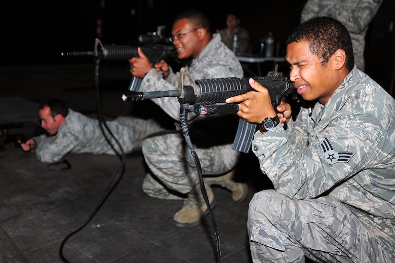 (Left to Right) Staff Sgt. Scott Stoffel, Tech. Sgt. Michael Dove, and Senior Airman Rafael Walden work through an attack scenario with the 51st Security Forces Squadron's Engagement Skills Trainer 2000 at Osan Air Base, Republic of Korea, Oct. 4, 2012. The group went through several scenarios on a virtual trainer that allowed them to differentiate between hostile and non hostile forces. Stoffel, Dove and Walden are 51st Civil Engineer Squadron Explosive Ordinance Disposal technicians. (U.S. Air Force photo/Airman 1st Class Alexis Siekert)