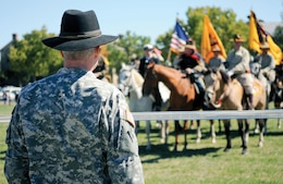 Brig. Gen. Donald M. MacWillie, senior commander, Fort Riley, watches the colors stop before him during a pass in review Sept. 22 at Fort Riley's Artillery Parade Field, as part of the close of the U.S. Cavalry Association's National Cavalry Competition. Soldiers from six posts and civilian historians from across the country attended the yearly event from Sept. 19 to 22, which was in conjunction with Fort Riley's Fall Apple Day Festival.  Photo by: Amanda Kim Stairrett, 1ST INF. DIV.