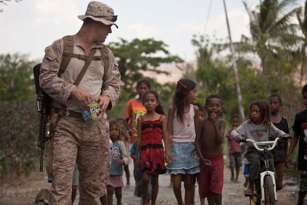 A U.S. Marine from Battalion Landing Team 3/5, 15th Marine Expeditionary Unit,  hands candy out to children during a presence patrol as part of Exercise Crocodilo in Metinaro, Timor-Leste, October 12, 2012. Throughout the exercise forces will participate in various field exercises and community relations aimed at strengthening the relationship between US and Timor-Leste. (U.S. Marine Corps photo by Cpl. Bobby J. Gonzalez)