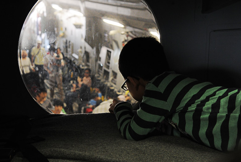 """A Korean boy peers through a flight deck window into the cargo bay of a C-17 Globemaster III from the 15th Wing at Joint Base Pearl Harbor-Hickam, Hawaii, during the """"Air Power Day"""" air show Oct. 20 at Osan Air Base, Republic of Korea. Consisting of aircrew members from the 535th Airlift Squadron at JBPHH, the demonstration team operating the C-17 fulfills a rare mission of showcasing C-17 capabilities at air shows in the Pacific theater and western United States. (U.S. Air Force photo by Senior Airman Lauren Main)"""