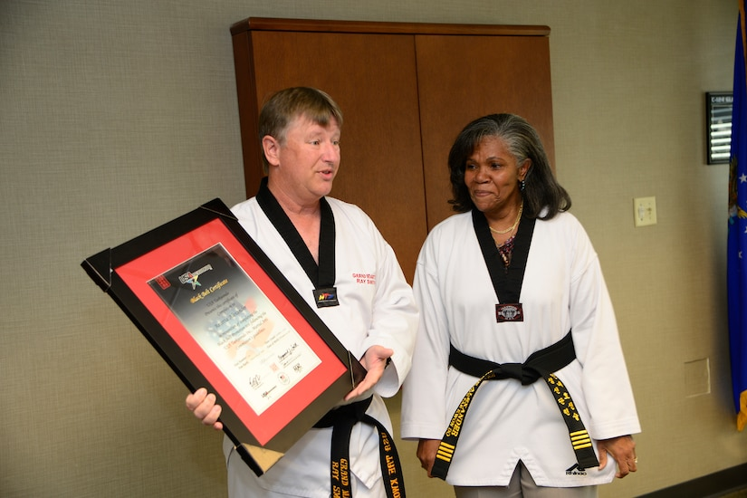 Grand Master Ray Smith, 8th degree Taekwondo black belt, presents the official USA Taekwondo honorary black belt certificate to Rose Alexander, 628th Air Base Wing chief of external information, at Joint Base Charleston – Air Base, S.C. Oct. 22, 2012. USA Taekwondo is a nationally recognized organization and affiliate of the U.S. Olympic team.  (U.S. Air Force photo / Staff Sgt. Rasheen Douglas)