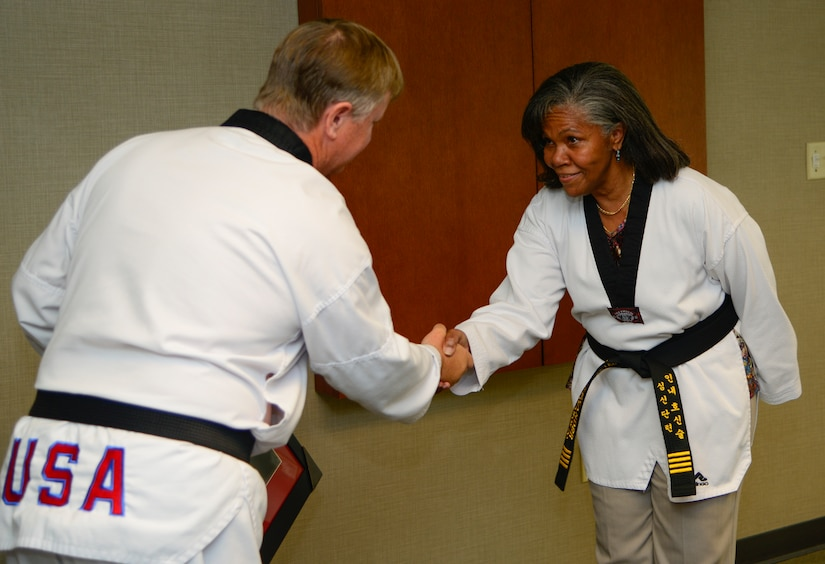 Rose Alexander, 628th Air Base Wing chief of external information, accepts her honorary black belt from Grand Master Ray Smith, 8th degree Taekwondo black belt, at Joint Base Charleston – Air Base, S.C. Oct. 22, 2012. Alexander's son, Charles Alexander, is a nationally recognized Taekwondo black belt and her grandson, Alexander Cheatham, although legally blind, has excelled in Taekwondo . (U.S. Air Force Photo / Staff Sgt. Rasheen Douglas)
