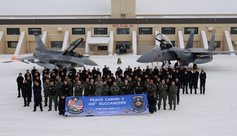 """Personnel from the 428th Fighter Squadron pose for a group photo on the final day of the RED FLAG-ALASKA 13-1 exercise Oct19, 2012 at Eielson Air Force Base, Alaska. The 428th FS """"Buccaneers"""" are stationed at Mountain Home Air Force Base, Idaho, as part of a unique, long-term partnership with the Republic of Singapore Air Force and have spent the past two weeks training in a simulated combat environment. (U.S. Air Force photo/Senior Airman Benjamin Sutton)"""