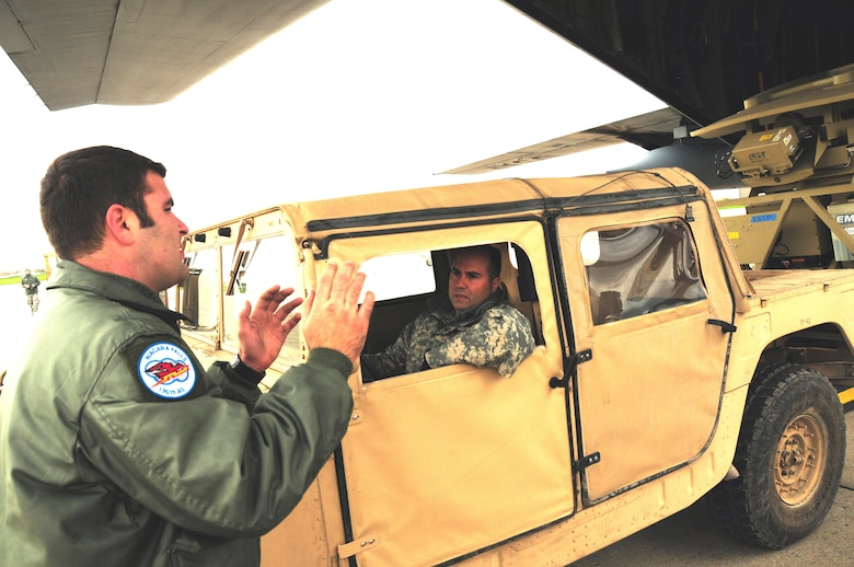 The Operational Company of the 42nd Infantry Division of the Army National Guard arrived ready to train with the 107th Airlift Wing's C-130 loadmasters. Senior Airman Babirad guides the AN/TSC-185 Satellite Vehicle onto the C-130 aircraft. Army Guard Sgt. 1st Class Anzalone is  behind the wheel of the HMMWV. Oct. 20, 2012 (U.S. Air Force Photo/Senior Master Sgt. Ray Lloyd)
