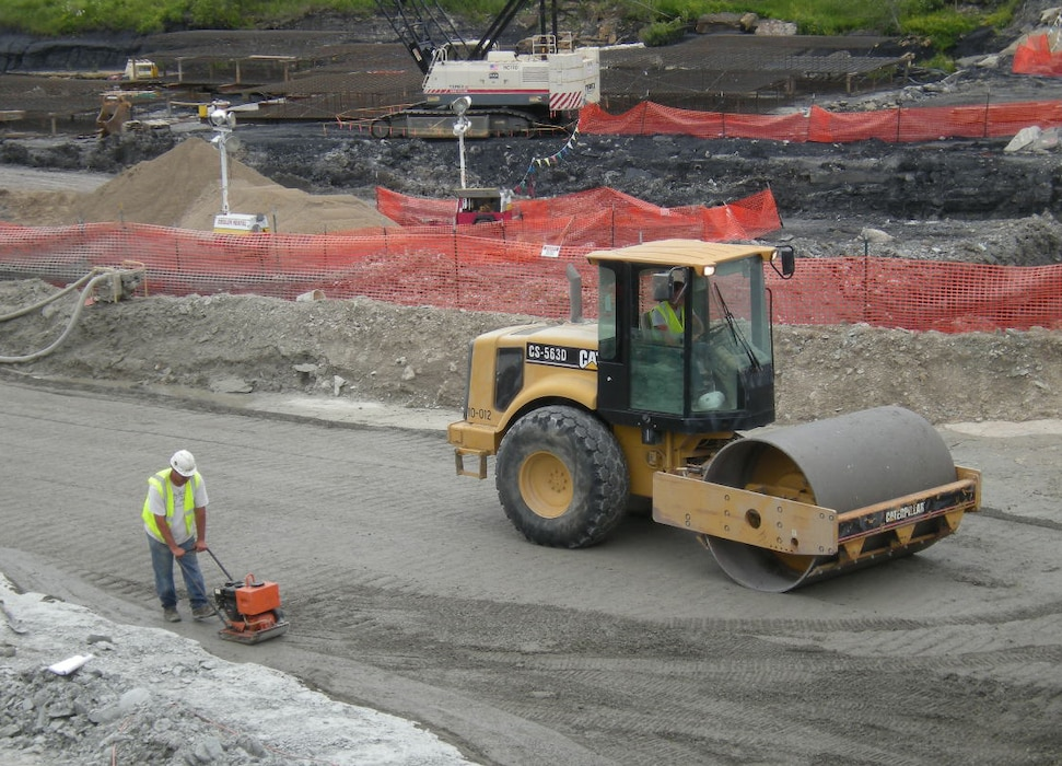 A contractor compacts roller-compacted concrete just days before water overtopped the spillway at Saylorville Lake in June 2010.