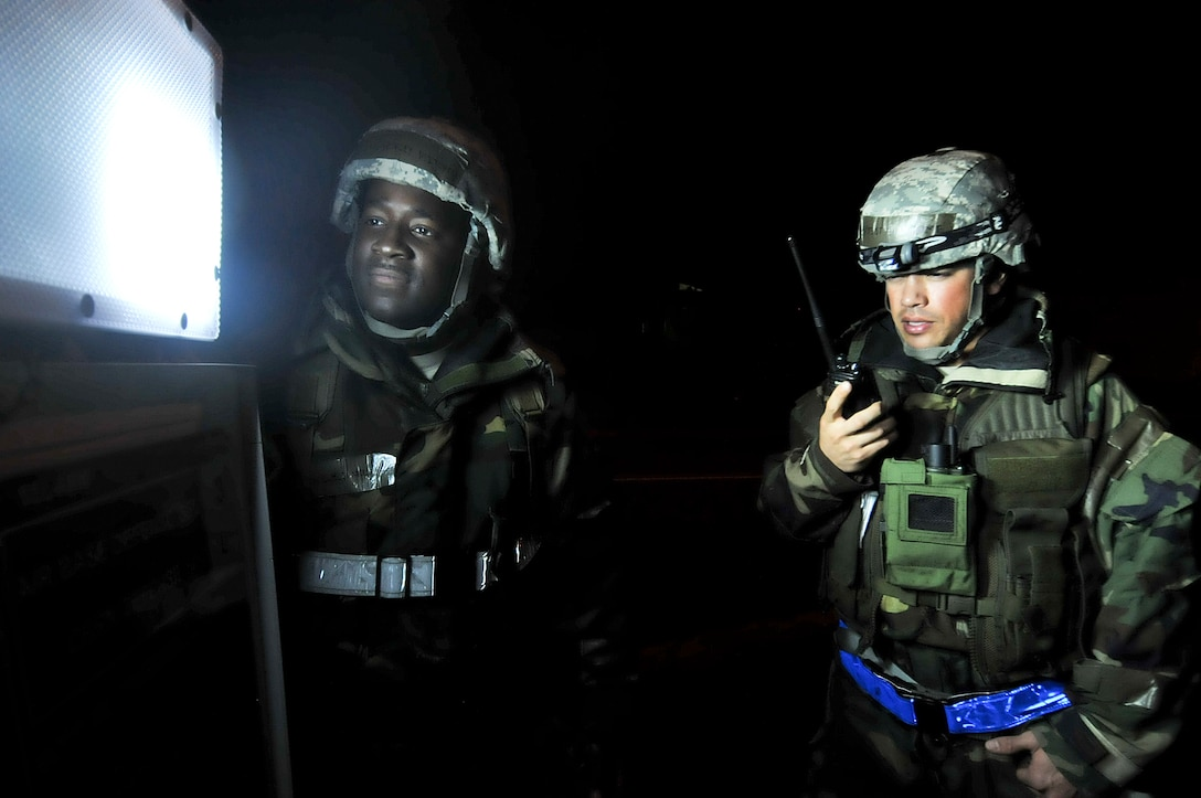 U.S. Air Force Staff Sgt. Chauncey Mitchell, 18th Civil Engineer Squadron readiness support team member, updates the MOPP transition point as U.S. Air Force Tech. Sgt. Giles Dame, 18th Civil Engineer Squadron readiness support team member, passes the information to their office during the fifth day of a Pacific Air Forces readiness inspection on Kadena Air Base, Japan, Oct. 24, 2012. This inspection will test the 18th Wing on its ability to survive and operate in a contingency. The readiness support teams ensures that Kadena are informed about the chemical conditions of each zone and checks each zones to ensure it isn't contaminated. (U.S. Air Force photo/Staff Sgt. Darnell T. Cannady)