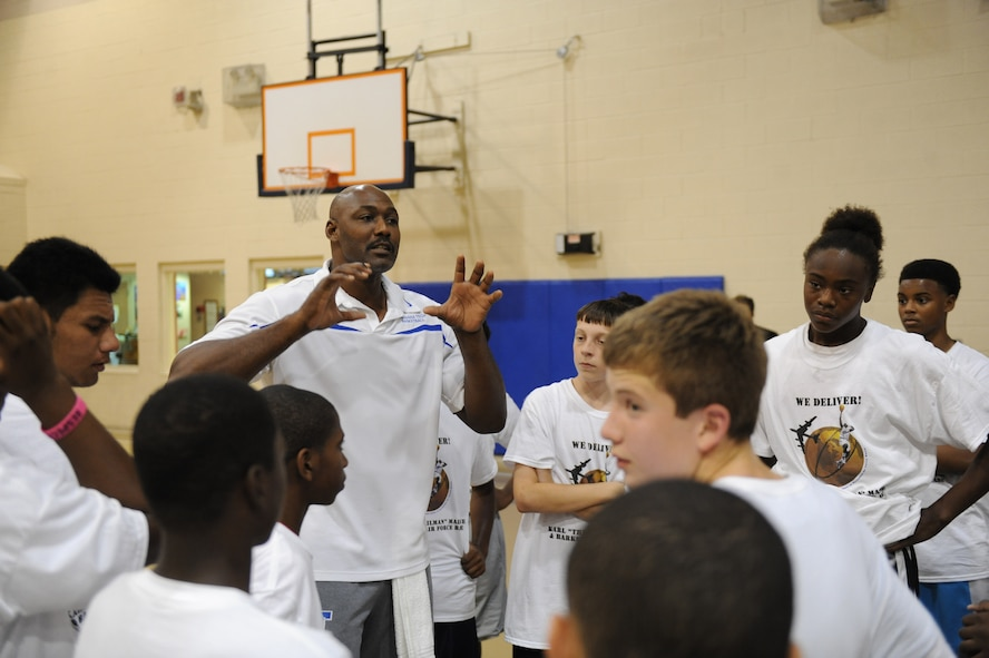 Karl Malone, retired NBA player, speaks to some of Barksdale?s youth about the fundamentals of basketball on Barksdale Air Force Base, La., Oct. 20. Participants in the clinic were able to learn drills, participate in team building exercises, compete in a shooting contest, scrimmage and have a photo taken with Malone. (U.S. Air Force photo/Senior Airman Micaiah Anthony)(RELEASED)