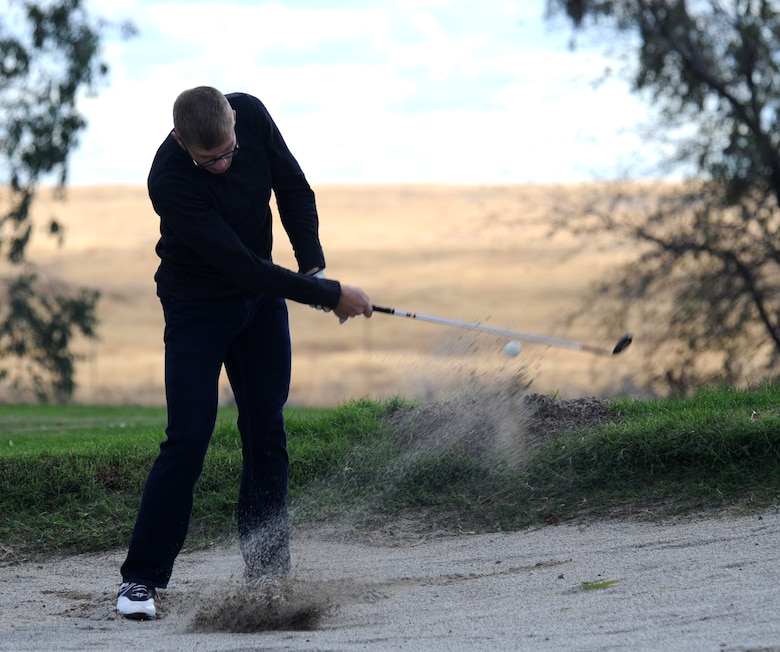Senior Airman Alan Crossley, 9th Mission Support Group, takes a shot out of a sand bunker during the Intramural Golf Championships at Coyote Run Golf Course Beale Air Force Base, Calif., Oct. 23, 2012. The championship consisted of 18 holes of match-play golf. (U.S. Air Force photo by Staff Sgt. Robert M. Trujillo/Released)