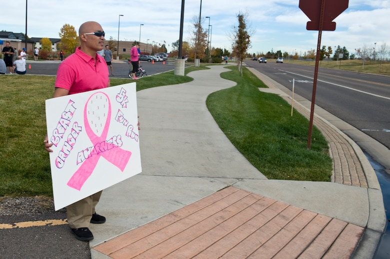 BUCKLEY AIR FORCE BASE, Colo. – Alan Muriera, Health and Wellness Center health and wellness director, cheers for racers as they complete the Breast Cancer Awareness 5K Run/Walk Oct. 19, 2012, near the fitness center. Competitors received pink lunch boxes and bracelets after the race. (U.S. Air Force photo by Airman 1st Class Riley Johnson)