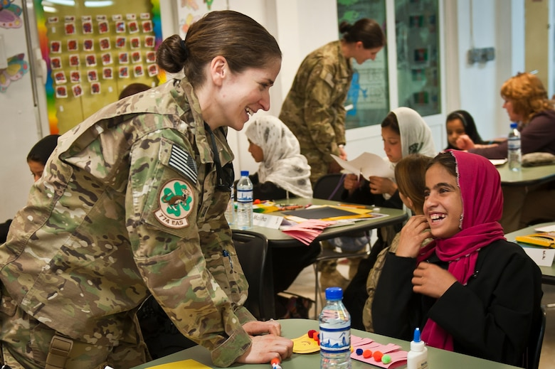 "Yagana, a local Afghan student, laughs with Capt. Rachel Seablom, a volunteer from the 774th Expeditionary Airlift Squadron, during a ""Cat in the Hat"" education session at Bagram Airfield, Afghanistan, Oct. 14, 2012. The program is a volunteer-run community outreach effort designed to provide local Afghan children a safe, nurturing learning environment in which they are inspired to bring positive change to Afghanistan. (U.S. Air Force photo/Capt. Raymond Geoffroy)"