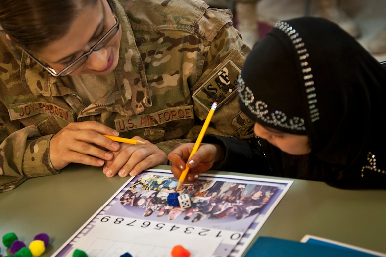 "Yagana, a local Afghan student, and Capt. Angela Joy-Radden, a volunteer from the 455th Expeditionary Operations Support Squadron, play a counting game together during a ""Cat in the Hat"" education session at Bagram Airfield, Afghanistan, Oct. 14, 2012. Bagram volunteers come out every week to mentor and educate local youth. (U.S. Air Force photo/Capt. Raymond Geoffroy)"