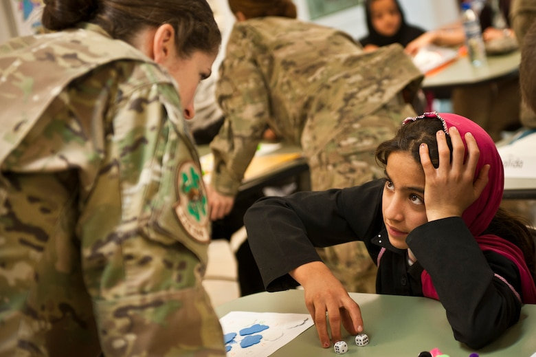 "Yagana, a local Afghan student, plays a counting game with Capt. Rachel Seablom, a volunteer from the 774th Expeditionary Airlift Squadron, during a ""Cat in the Hat"" education session at Bagram Airfield, Afghanistan, Oct. 14, 2012. The program is a volunteer-run community outreach effort designed to provide local Afghan children a safe, nurturing learning environment in which they are inspired to bring positive change to Afghanistan. (U.S. Air Force photo/Capt. Raymond Geoffroy)"