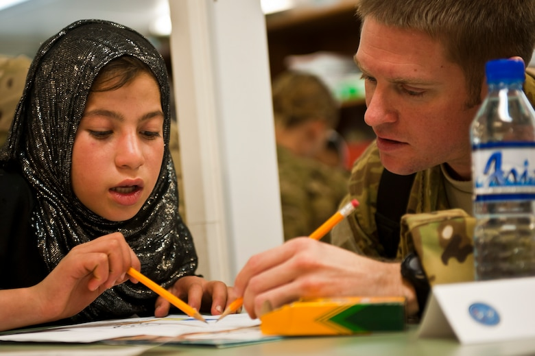 "Muzghan, a local Afghan student, and Capt. Leonard Spigiel, a volunteer from the 774th Expeditionary Airlift Squadron, work on a project together during a ""Cat in the Hat"" education session at Bagram Airfield, Afghanistan, Oct. 14, 2012. The educational outreach program supports the International Security Assistance Force's counter-insurgency efforts by enabling positive interaction between U.S. service members and the local community. (U.S. Air Force photo/Capt. Raymond Geoffroy)"