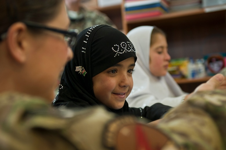"Yagana, a local Afghan student, and Capt. Angela Joy-Radden, a volunteer from the 455th Expeditionary Operations Support Squadron, review the alphabet together during a ""Cat in the Hat"" education session at Bagram Airfield, Afghanistan, Oct. 14, 2012. Bagram volunteers come out every week to mentor and educate local youth. (U.S. Air Force photo/Capt. Raymond Geoffroy)"