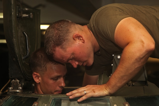 Corporals Stuart C. Stroman (left), and Evan L. Watson, both amphibious assault vehicle crew chiefs with AAV Platoon, India Company, Battalion Landing Team 3/5, 15th Marine Expeditionary Unit, perform routine maintenance on an AAV in the well deck of the USS Green Bay, Oct. 17. In order to bring the Marines of India Co. to shore, the company's AAV Platoon puts in countless hours toward achieving readiness with their AAVs. India Co. is one of three rifle companies that make up BLT 3/5, the 15th MEU's ground combat element. The 15th MEU is currently embarked as part of the Peleliu Amphibious Ready Group, while they serve as the nation's rapid-response sea-based Marine Air Ground Task Force for Western Pacific Deployment 12-02. Stroman, 21, is from Bloomington, Minn., and Watson, 27, is from West Hills, Calif.