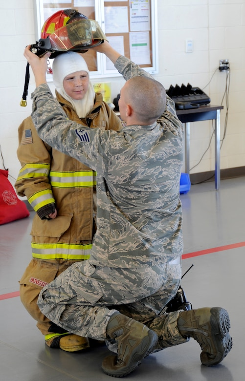 U.S Air Force Staff Sgt. Cole Connors, 355th Civil Engineer Squadron firefighter, assists Larry Ronstadt into fire-fighting personal protective equipment on Oct 25, 2012, during Larry's tour of the base Fire Department, as part of the Pilot for a Day program at Davis-Monthan Air Force Base, Ariz.  Larry was an honorary 357th Fighter Squadron pilot, where he, his father and grandfather toured the squadron, visited an A-10 static and simulator, an HH-60 static and the base Fire Department.  Sergeant Connors is a Firefighter Crew Chief with the base Fire Department. (U.S. Air Force photo by 1LT Susan Harrington/released)